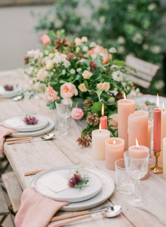 a romantic wedding tablescape with peachy candles and napkins, peachy and orange blooms, greenery and cutlery with peachy handles