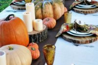 a rustic fall bridal shower setting with large natural pumpkins, pillar candles on wood slices and colorful napkins