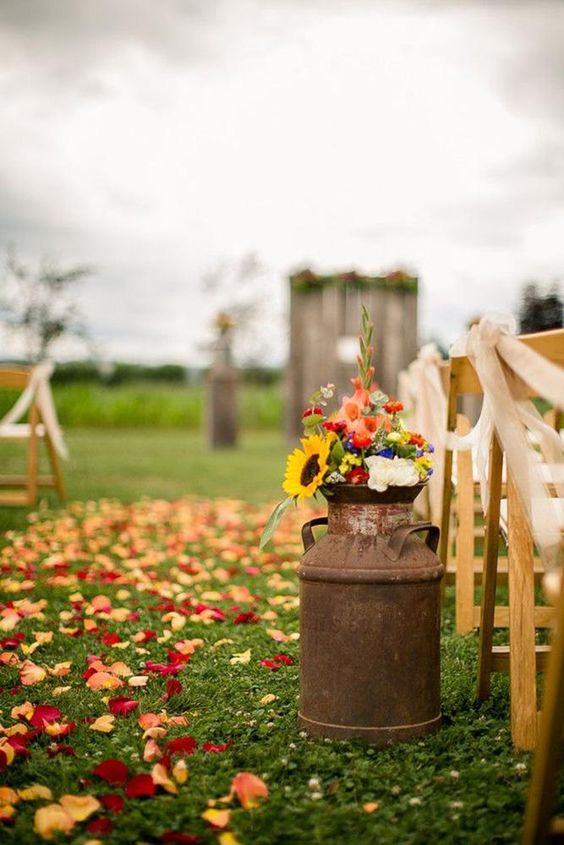 a rustic fall wedding aisle with colorful petals, a rusty churn with bold blooms and greenery is a cool and lovely idea
