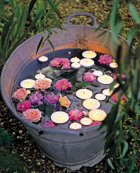 a rustic wedding decoration - a glavanized bathtub with floating blooms and candles is a lovely and easy to realize idea