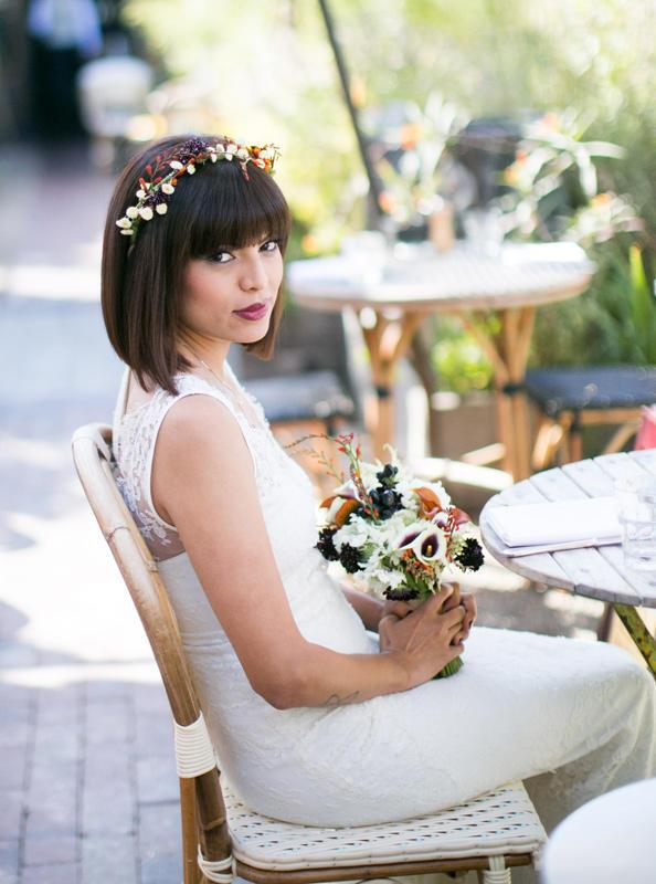a short bob with bangs and a fresh bloom and berry hairpiece for a modern bride with a bit of edge