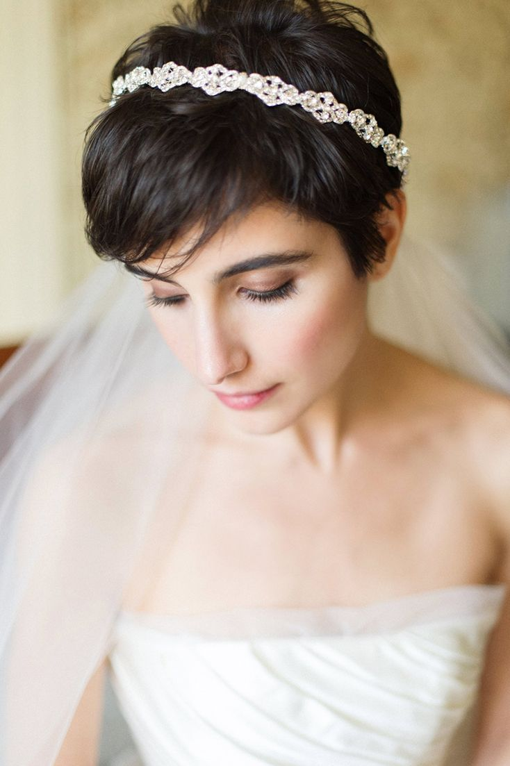 a short pixie haircut with bangs and a rhinestone hairpiece plus a veil