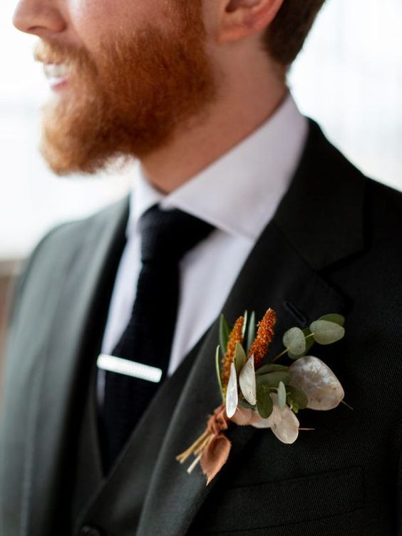 a simple and pretty fall wedding boutonniere with rust blooms, green leaves and lunaria plus a rust ribbon for a modern or rustic wedding