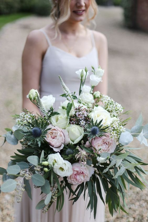 a spring wedding bouquet of blush and white peonies and roses, astilbe, thistles and greenery is a chic and very delicate idea