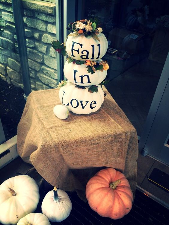 a stack of white pumpkins decorated with blooms, foliage and letters as a fall bridal shower decoration