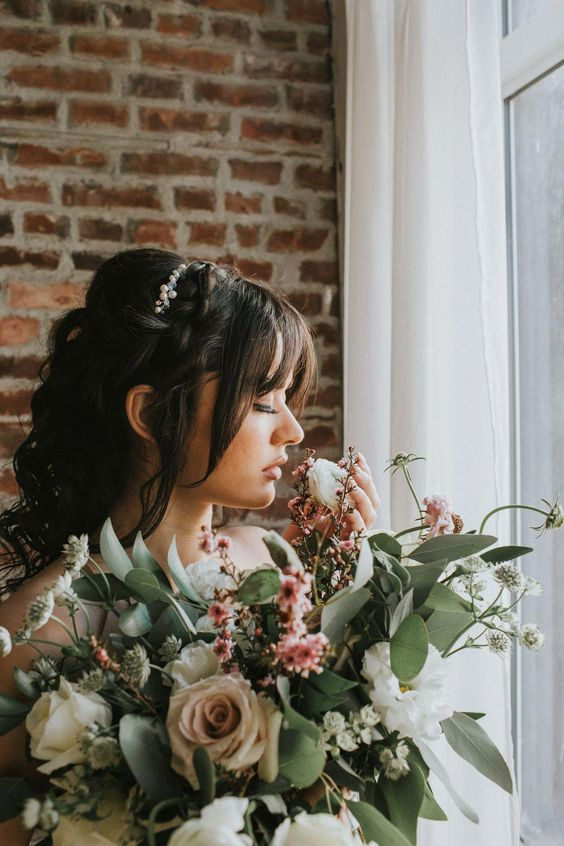 a stylish wedding half updo with curls down, a braid on top and some bangs
