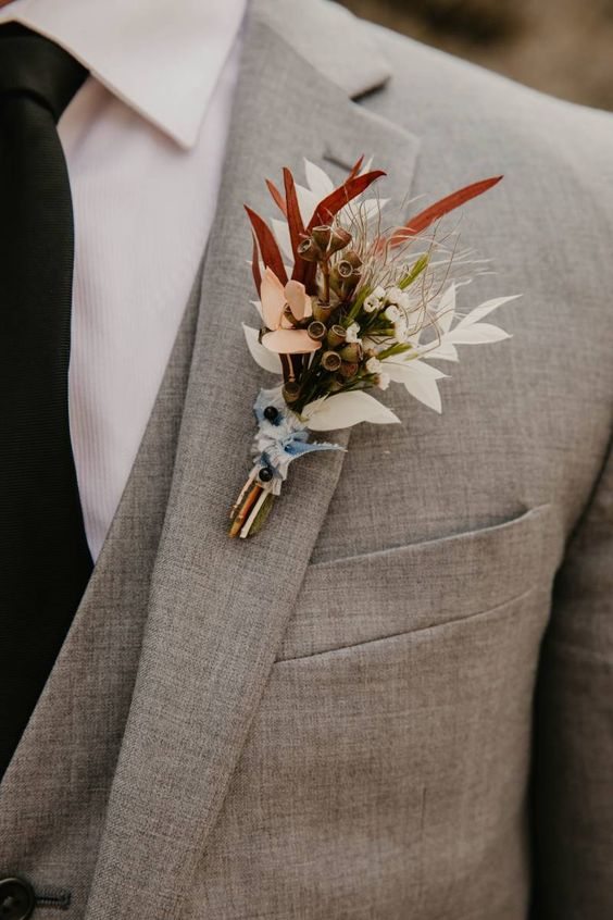 a textural fall wedding boutonniere with neutral and pastel blooms, grasses and bold leaves is a pretty idea for a modern wedding