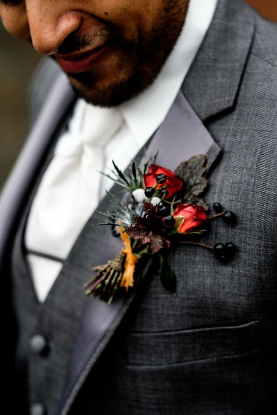 a textural fall wedding boutonniere with red blooms, privet berries, thistles and some dark leaves is a fun and catchy idea
