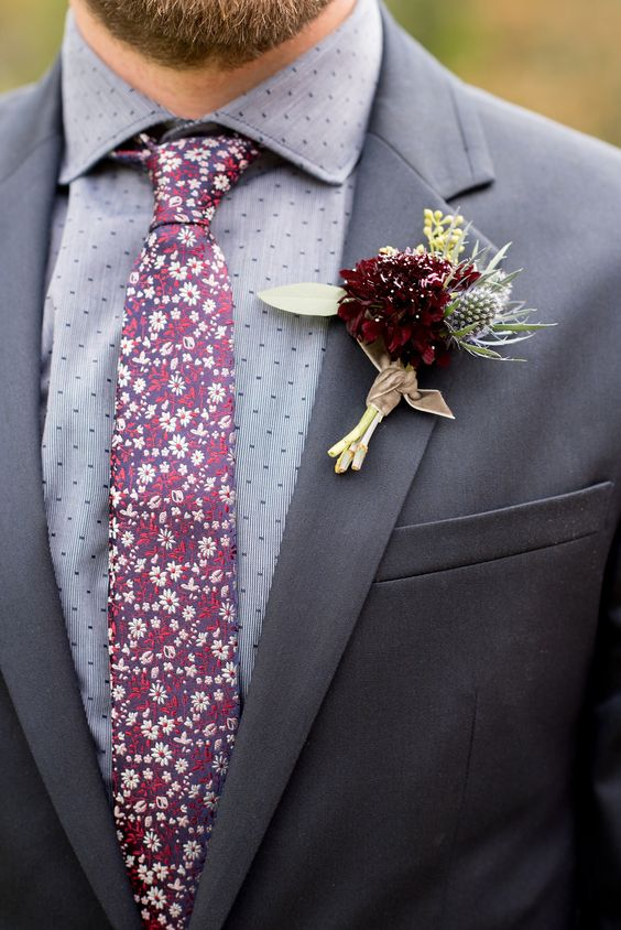 a textural wedding boutonniere with a burgundy bloom, a thistle and some greenery for a moody boho fall wedding