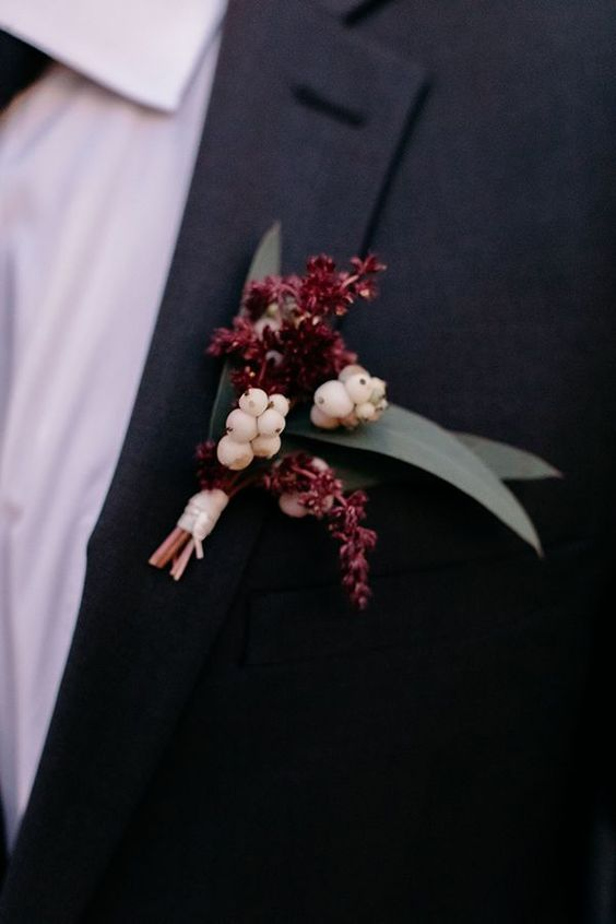 a timeless fall wedding boutonniere with burgundy blooms and white berries plus simple leaves is amazing
