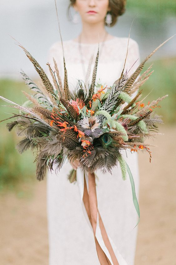a unique wedding bouquet of feathers, greenery and some blooms plus long ribbons is a lovely and statement idea for a boho bride