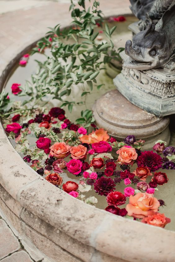 a vintage fountain styled with floating burgundy, orange, red and hot pink blooms and greenery for a lovely wedding