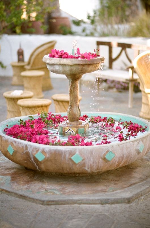 a vintage fountain with floating hot pink blooms is a lovely idea for an outdoor wedding, they will add color