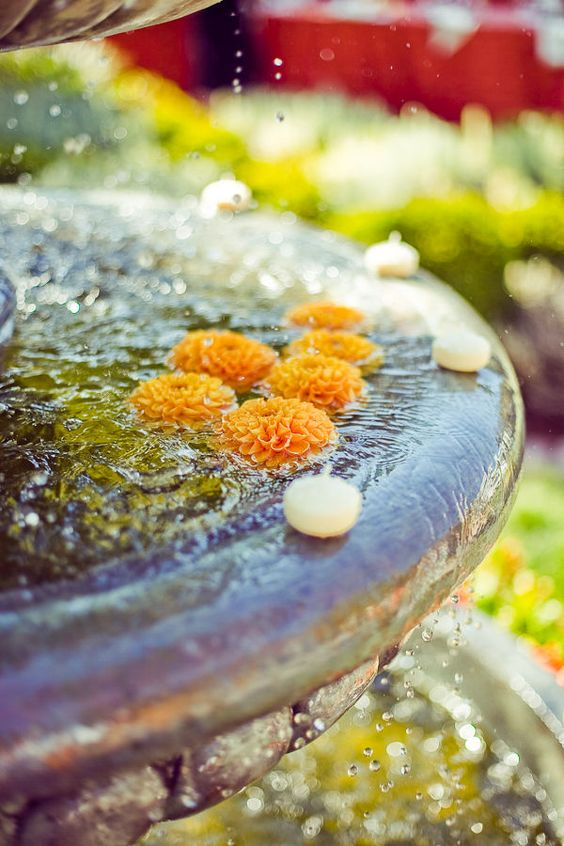 a vintage fountain with floating orange dahlias and candles is a very bright and easy outdoor decor idea