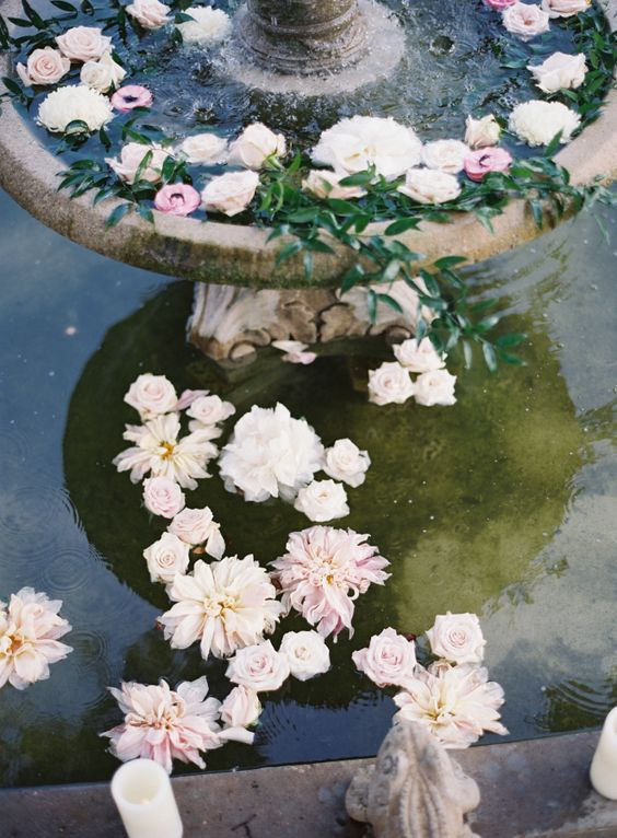 a vintage fountain with floating pastel blooms and candles on the edge is a beautiful and chic idea to go for