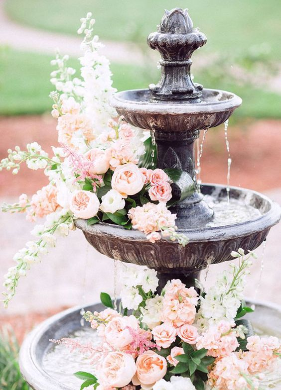 a wedding fountain with pink roses and peonies floating in it looks very chic, refined and romantic