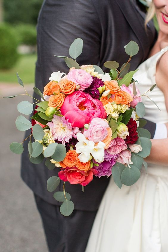 a whimsy and bright wedding bouquet of coral peonies, pink, orange, yellow and white blooms and eucalyptus is amazing