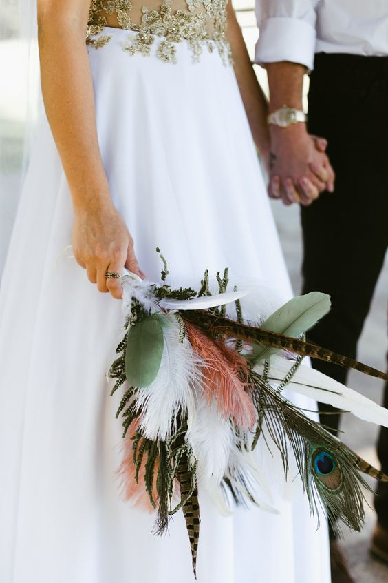 a whimsy boho wedding bouquet with feathers and leaves is a very creative solution for a fairy-tale or boho wedding