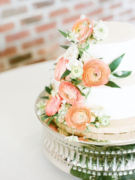 a white wedding cake with peachy pink and orange blooms and white ones plus greenery for a refined wedding