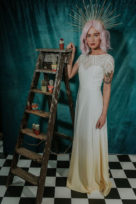 an A-line dip dye wedding dress with a lace bodice and cap sleeves, a yellow skirt, pink hair and a bold headpiece