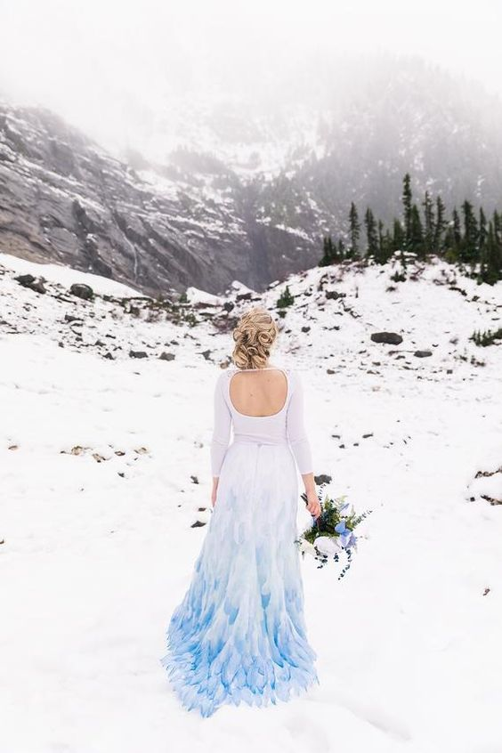 an A-line dip dye white and blue wedding dress with a cutout back and long sleeves is a chic idea