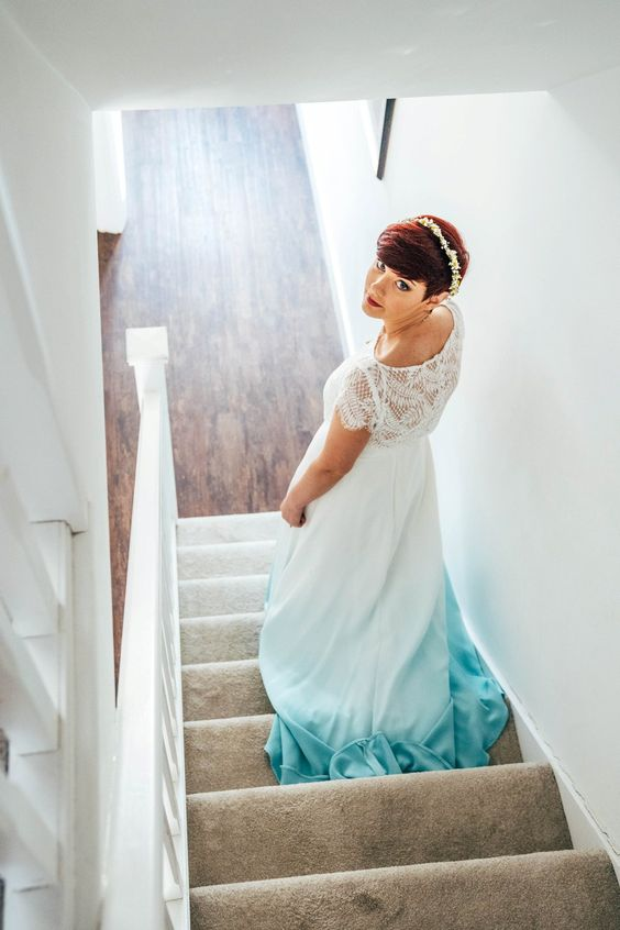 an A-line wedding dress with a lace bodice and cap sleeves plus a dip dye blue skirt and an embellished headpiece