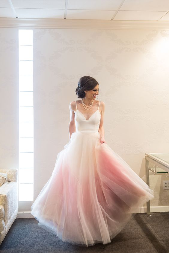 an A-line wedding dress with a white bodice with spaghetti straps and a dip dye layered pink skirt