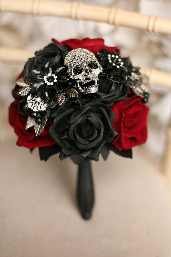 an elegant black and red silk rose wedding bouquet with vintage brooches and an embellished skull is ideal for a Halloween wedding