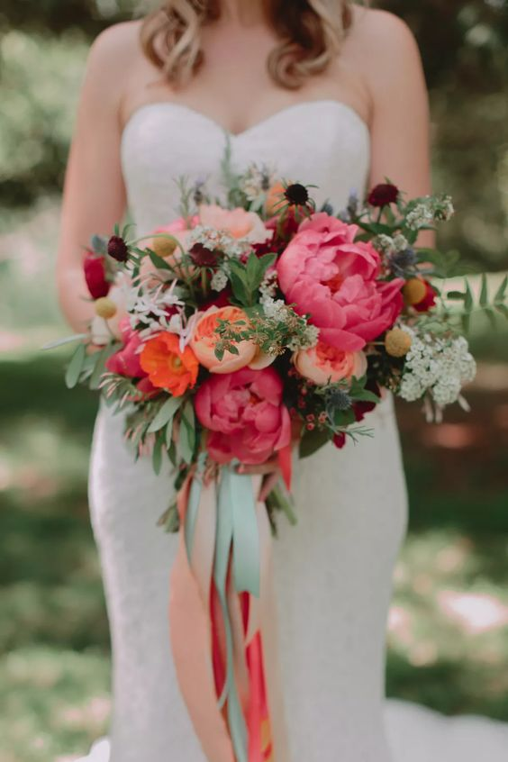 an elegant bright wedding bouquet of coral peonies, blush ones, greenery, white and dark blooms for a fall wedding