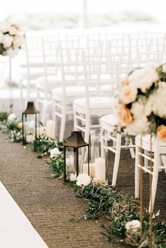 an elegant fall wedding aisle lined up with neutral blooms, greenery and candle lanterns plus lush neutral floral arrangements