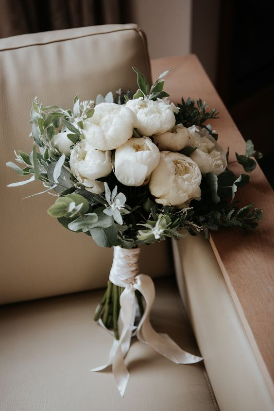 an elegant white peony and greenery wedding bouquet is perfect for a neutral wedding in any season