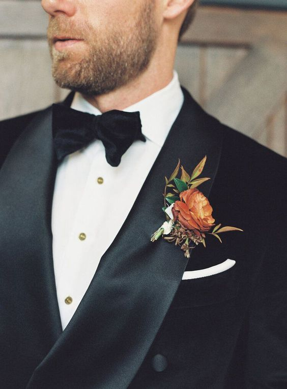 an exquisite fall wedding boutonniere with leaves and a single rust bloom is  a stylish and beautiful idea