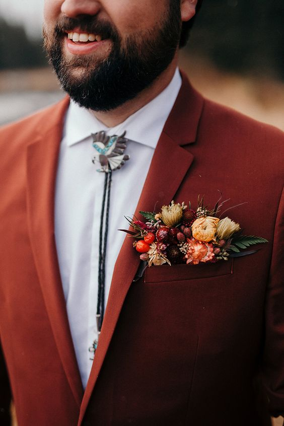 fall pocket square styling with yellow, orange blooms and leaves and berries for a fall boho wedding