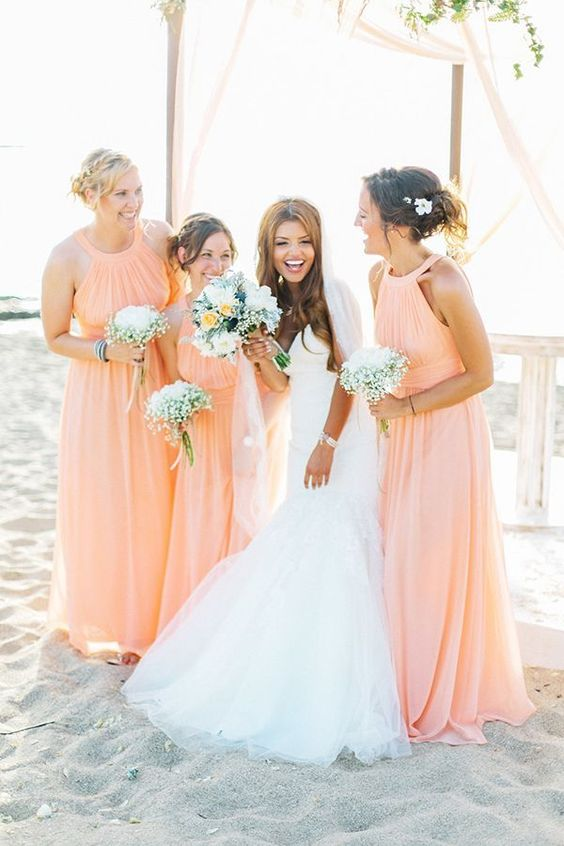 pretty halter neckline peachy pink maxi bridesmaid dresses with criss cross sashes and pleated bodices for a beach wedding