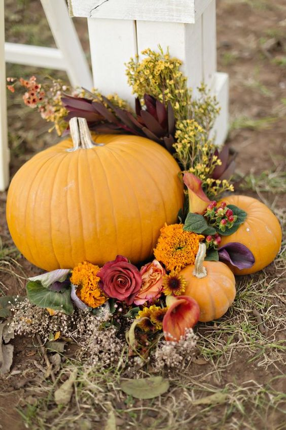 rustic fall wedding aisle decor with bold pumpkins, blooms and some leaves is a simple and cool arrangement to rock
