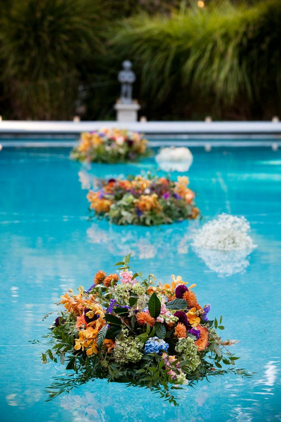 super bright floral and greenery arrangements floating in the pool will make your outdoor wedding decor veyr impressive