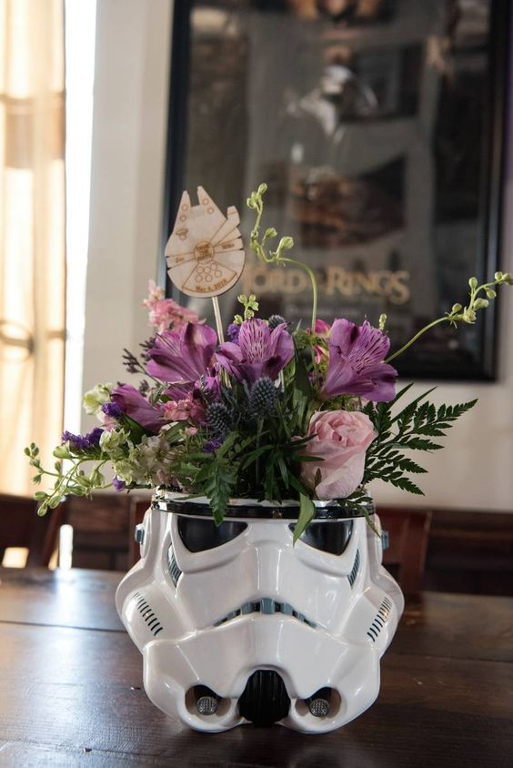 a Stormtrooper helmet with bright blooms and a little wood burnt ship touch is a cool centerpiece for a wedding