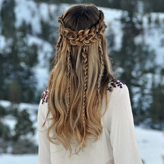 a Viking-inspired half updo with a large braided halo, with braids down and waves down is a chic idea for a boho bride