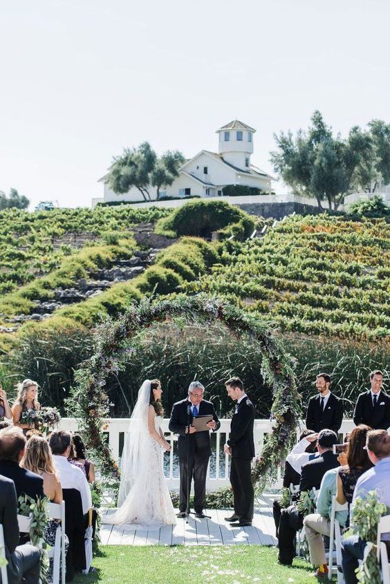 a beautiful fall vineyard wedding ceremony space with a trendy round greenery wedding arch and greenery decorating aisle chairs
