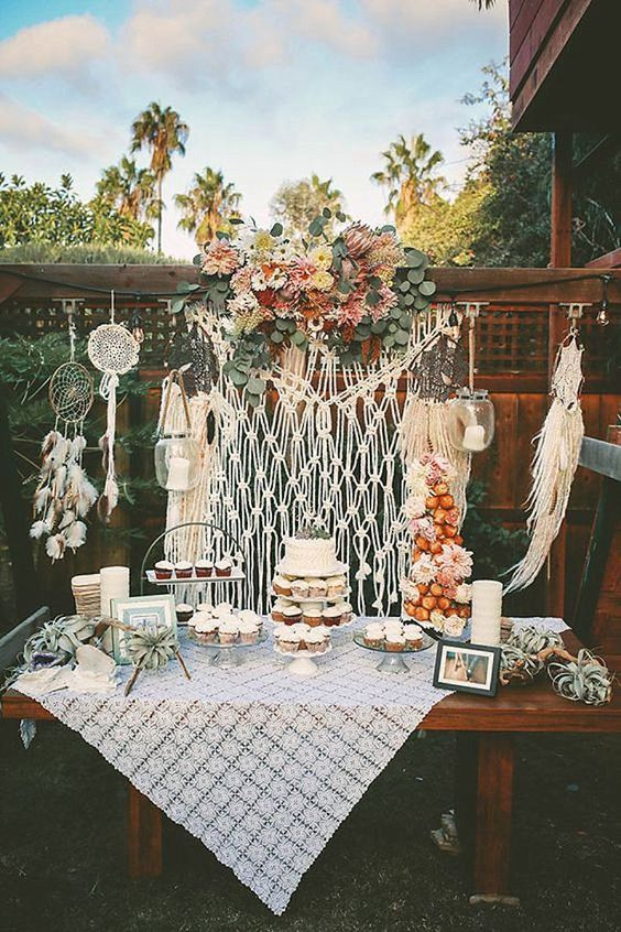 a boho dessert table with a macrame hanging, a doily tablecloth, some dreamcatchers, air plants and blooms
