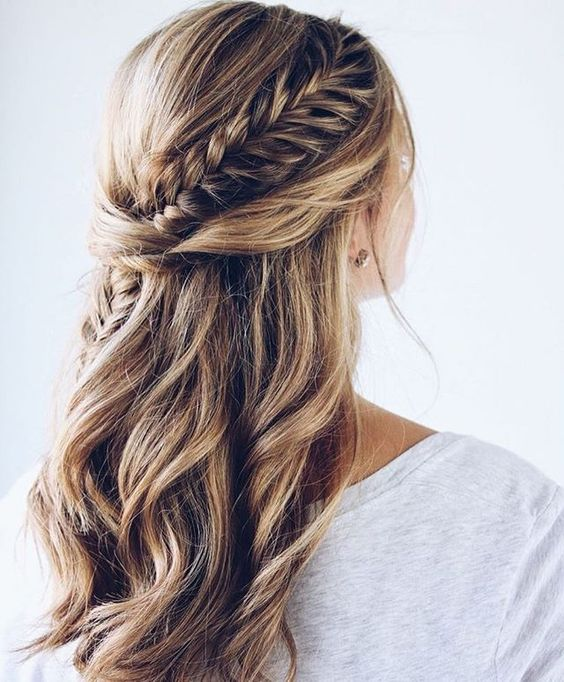 a boho wedding hairstyle with a fishtrail braid coming from the front to the back and twists plus waves down