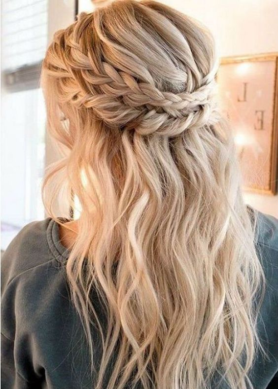 a boho wedding half updo with a messy voluminous top, a double braided halo and waves down plus bangs