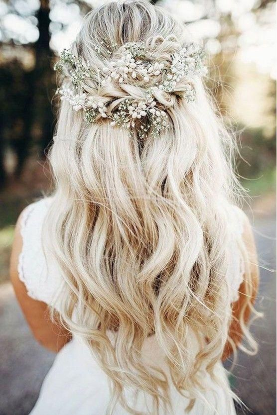 a boho wedding half updo with a volume on top, a braided part and waves down plus a pearl hairpiece and baby's breath