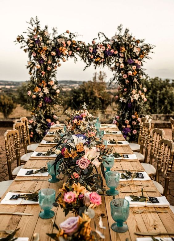 a bold vineyard wedding reception with bright florals and glasses, with an oversized lush floral arch is a cool idea