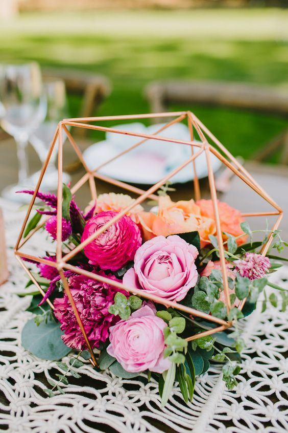 a bright geometric wedding centerpiece with pink and fuchsia blooms and greenery will fit many weddings