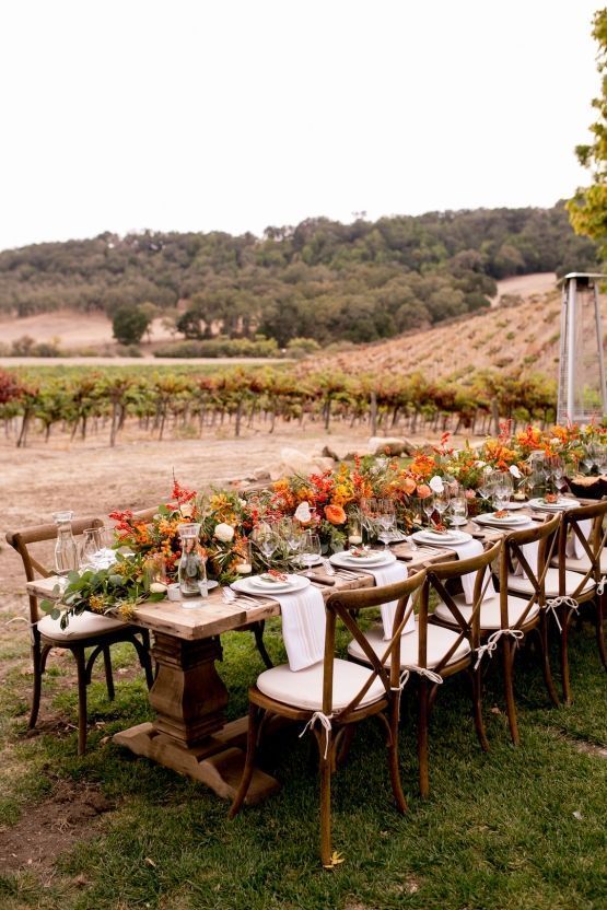 a bright harvest-inspired fall vineyard wedding reception with a vintage table and chairs outdoors, bodl blooms and berries