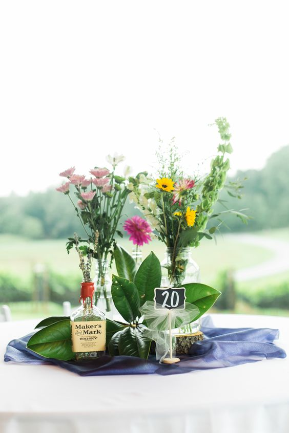 a bright summer wedding centerpiece of bottles and jars, bright wildflowers and greenery plus a table number