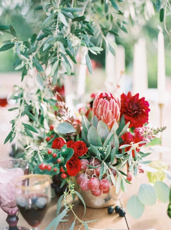 a bright vineyard wedding centerpiece of a gold vase, red blooms, a king protea, greenery and grapes