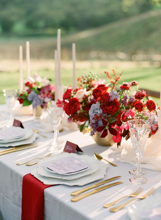 a bright vineyard wedding centerpiece of a gold vase with red and lilac blooms and some greenery