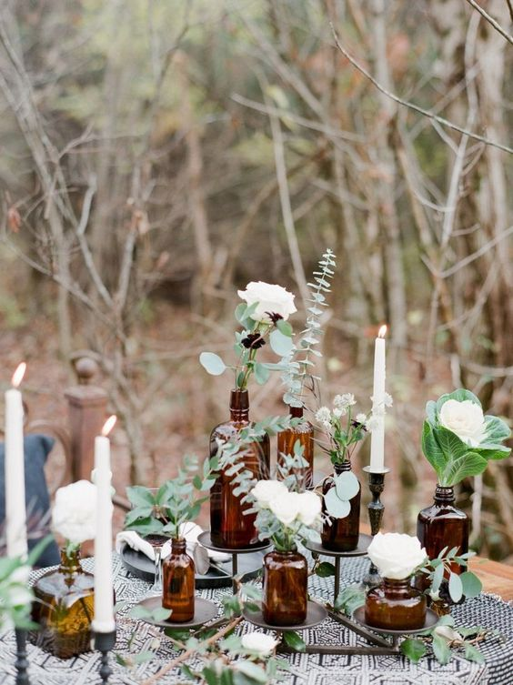 a catchy wedding centerpiece of apothecary bottles placed on stands and with white blooms and greenery in them